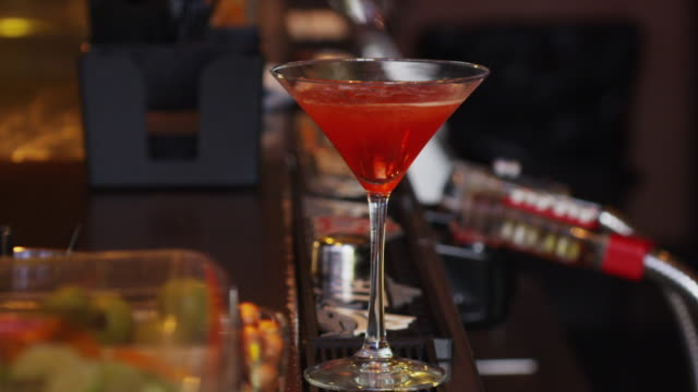 close up bartender's hands make a colorful martini with an orange slice and flower garnish. - cocktail stock videos & royalty-free footage