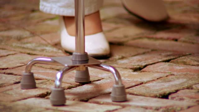 close up base of cane + feet of senior woman walking outdoors