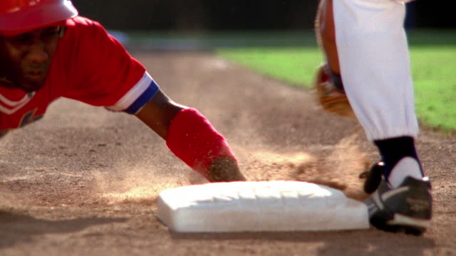 Close up baseball player sliding into base with fielder tagging him
