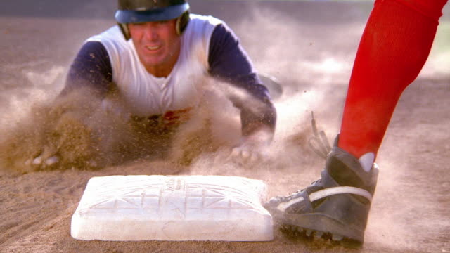 close up baseball player sliding into base with fielder tagging him and dirt flying - baseballspieler stock-videos und b-roll-filmmaterial