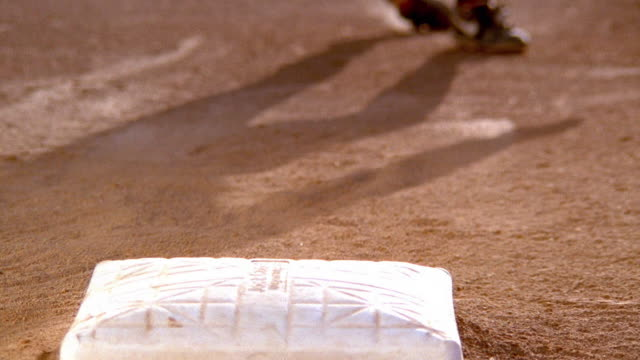 Close up baseball player sliding into base with fielder tagging him and dirt flying