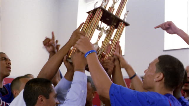 vidéos et rushes de close up basketball players raising trophy and cheering in locker room - award
