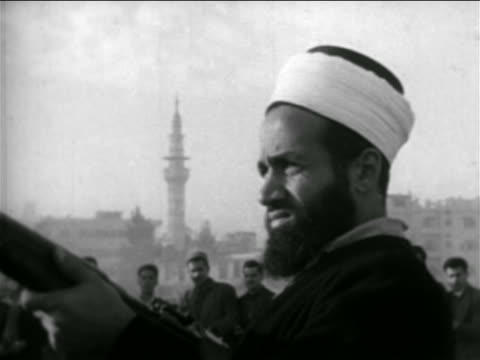 close up bearded man in hat holding rifle / syria / newsreel - 1957 stock-videos und b-roll-filmmaterial