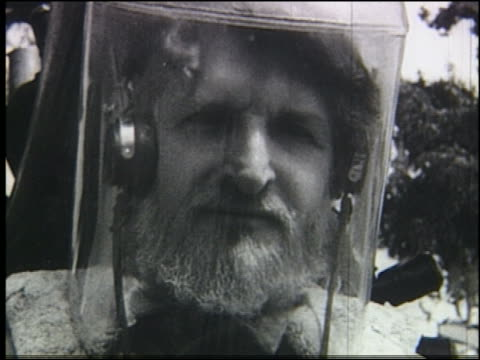 B/W close up bearded man in headphones + strange clear helmet