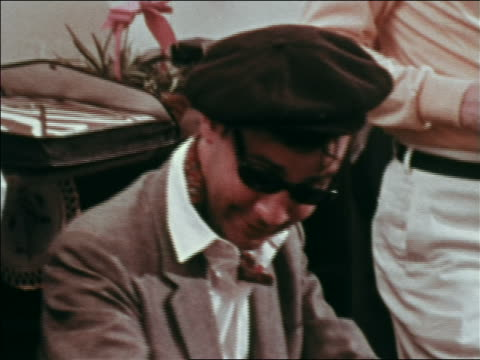 1969 close up beatnik man in beret, ascot + sunglasses smiling at party / greenwich village, nyc - cravat stock videos and b-roll footage