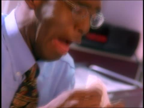 canted close up black businessman with eyeglasses sneezing - 若い男性だけ点の映像素材/bロール