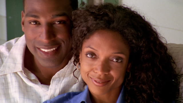 Close up Black couple cuddling and smiling