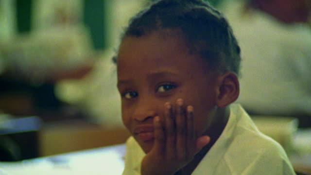 Close up Black girl sitting at desk and smiling at camera / South Africa