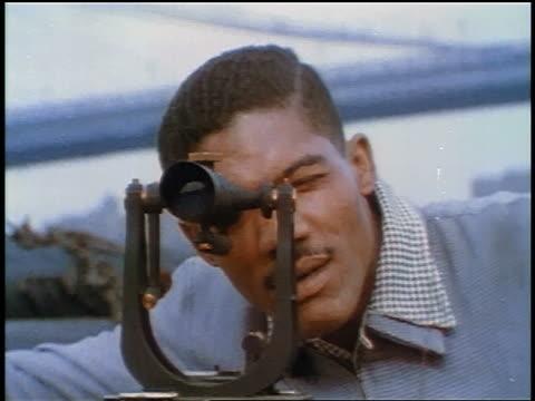 1957 close up black male surveyor looking through surveyors level - 1957 stock videos & royalty-free footage
