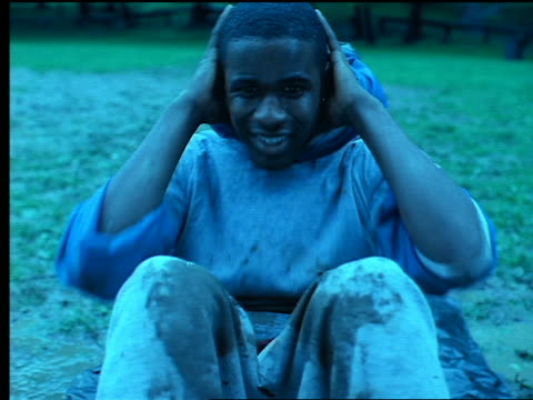BLUE close up Black man doing sit ups in mud outdoors