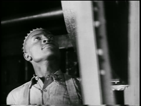 b/w 1932 close up black man looking up at parts moving on conveyor in ford car factory / industrial - 1932 stock videos and b-roll footage