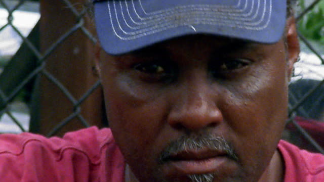 close up black man with blue baseball cap / chain link fence in background - baseball cap stock videos & royalty-free footage