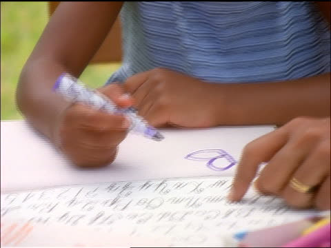 close up black mother helping young daughter wearing glasses write letters outdoors - pen stock videos & royalty-free footage