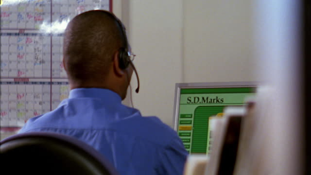 Close up Black office worker wearing headset turning to look over shoulder / smiling
