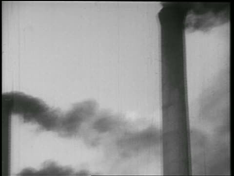 vídeos de stock e filmes b-roll de b/w 1939 close up pan black smoke emitting from row of factory smokestacks / documentary - lugar genérico