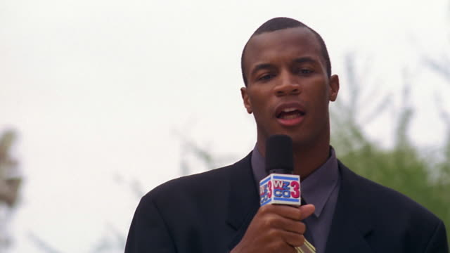 close up black television reporter raising microphone to mouth and talking outdoors - newsreader stock videos & royalty-free footage