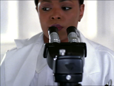 vidéos et rushes de close up black woman in lab coat looking into microscope - microscope