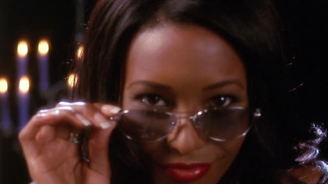 vídeos de stock e filmes b-roll de close up black woman lowering sunglasses / winking / candles in background - piscar
