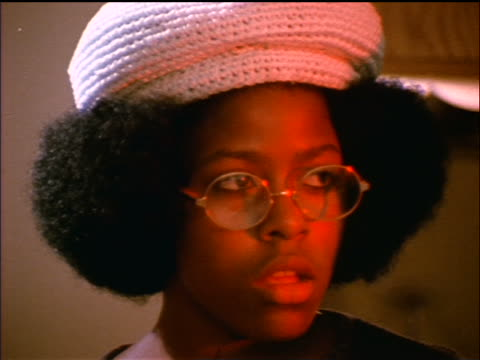 1974 close up Black woman with afro in hat + eyeglasses looking bored at party indoors / documentary