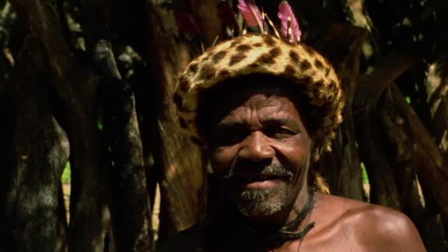Close up Black Zulu medicine man in hat smiling outdoors / Durban, KwaZulu-Natal, South Africa