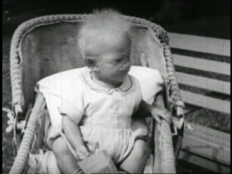 B/W 1928 close up blonde baby in bassinet throwing something offscreen / short
