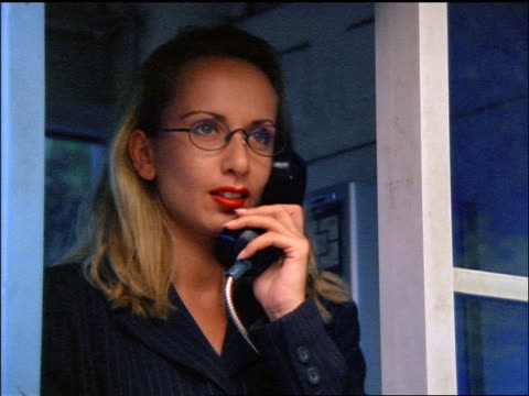 close up blonde businesswoman with eyeglasses talking on pay phone + checking watch / jakarta - 電話ボックス点の映像素材/bロール