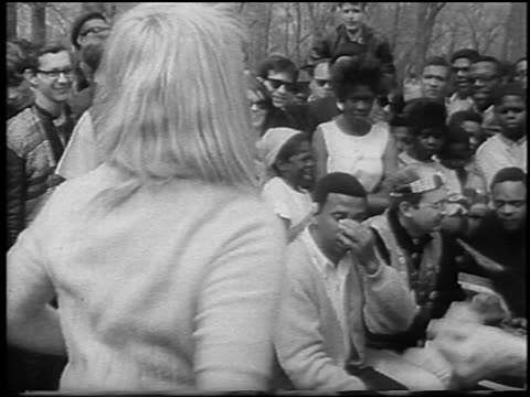 b/w 1967 close up blonde female hippie shaking hips while dancing / people watching in background / detroit - manifestante video stock e b–roll