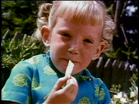 vídeos de stock e filmes b-roll de 1969 close up blonde girl eating french fry outdoors / industrial - lanche