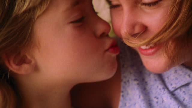close up blonde girl kissing smiling girl on cheek outdoors - sister stock videos & royalty-free footage