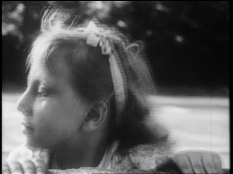 stockvideo's en b-roll-footage met b/w 1939 close up blonde girl looking around over wall / documentary - alleen meisjes