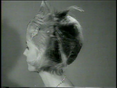 b/w 1960 close up blonde model with extraordinary hairstyle turning towards camera / newsreel - viraggio video stock e b–roll