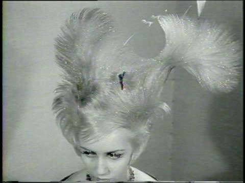 b/w 1960 close up blonde model with extraordinary hairstyle turning towards camera / newsreel - getönt stock-videos und b-roll-filmmaterial