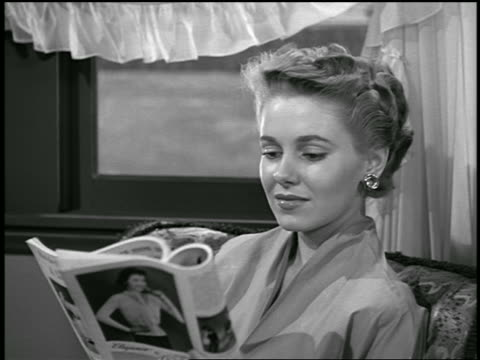 vidéos et rushes de b/w 1955 close up blonde woman sitting reading magazine / pan as she looks to air conditioner / industrial - magazine
