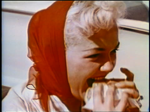 1958 close up blonde woman with red scarf on head eating hamburger outdoors / newsreel - ファーストフード点の映像素材/bロール