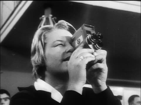 B/W 1960 close up blonde woman with small motion picture camera / Germany / newsreel
