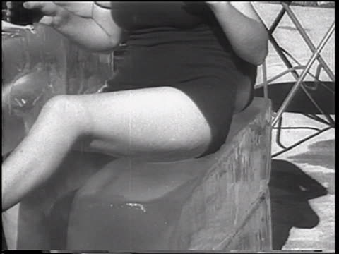 B/W 1933 close up body of woman wearing bathing suit sitting on large block of ice / Coney Island, NY