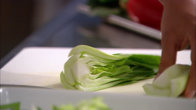 close up bok choy being chopped on cutting board / rack focus being lifted onto plate / auckland, new zealand - chopping stock videos & royalty-free footage