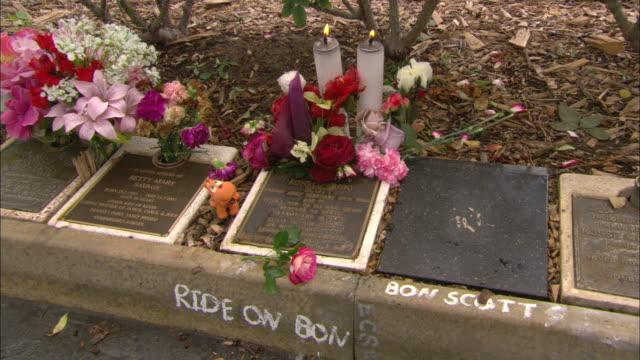 close up bon scott memorial star in pavement - tilt up to wide shot cemetery gravestones / bon scott memorial entrance gateway / candle placed beside... - フリーマントル点の映像素材/bロール