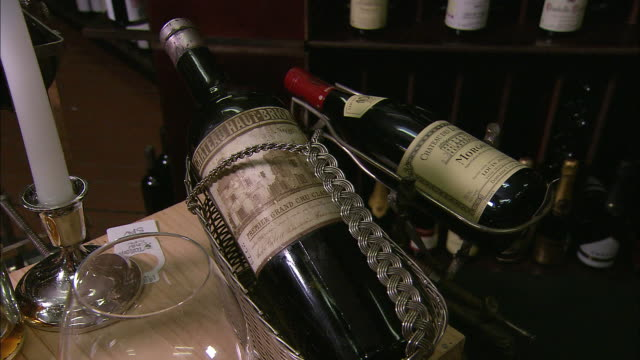 close up bottle of 1926 Chateau HautBrion Premier Grand Cru Classe / pan bottles of Penfolds Grange Hermitage on display stand / CU Penfolds 389...