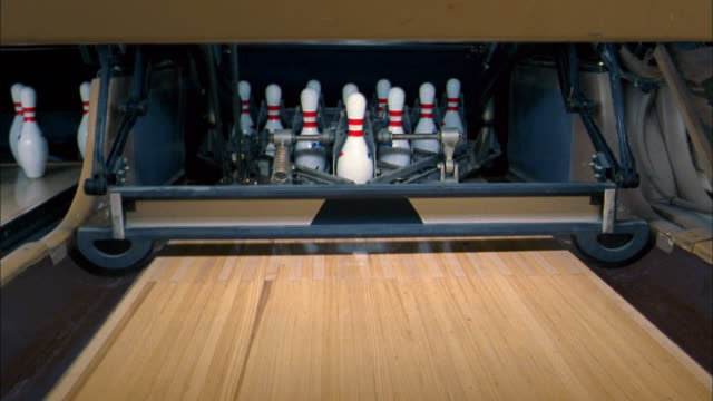 vidéos et rushes de close up bowling pins being reset by pin machine in bowling alley - rafraîchissement
