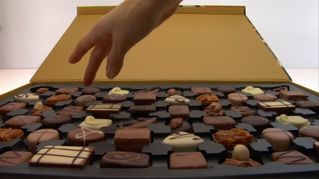 close up box of chocolates/ woman's hand choosing piece - scegliere video stock e b–roll