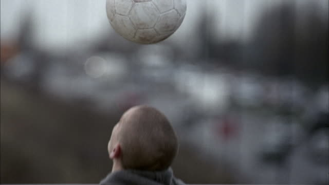 Close up boy bouncing soccer ball on head