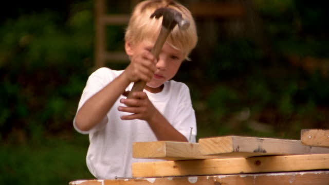 close up boy hammering nail into piece of wood - hammer stock videos and b-roll footage