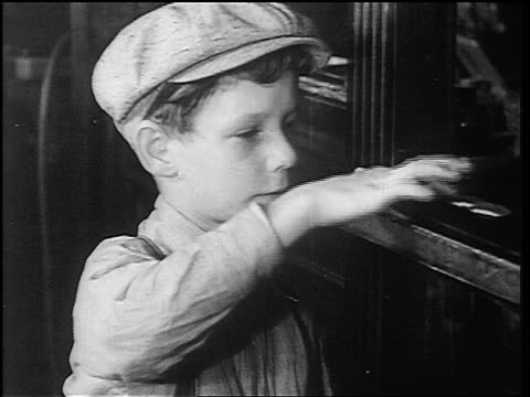 B/W 1934 close up boy in cap counting coins at teller window in Fon du Lac bank / East Peoria, IL / news.