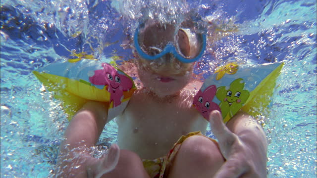 vídeos de stock e filmes b-roll de close up boy in scuba goggles and inflatable arm bands underwater giving thumbs-up to cam - piscina
