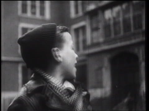 b/w 1939 close up boy in wool cap shouting off screen + pointing / nyc / documentary - documentary footage stock videos and b-roll footage