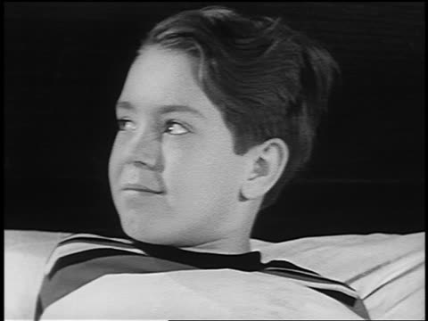 b/w 1953 close up boy lying in bed drinking medicine from spoon + water from glass - drinking glass stock videos & royalty-free footage