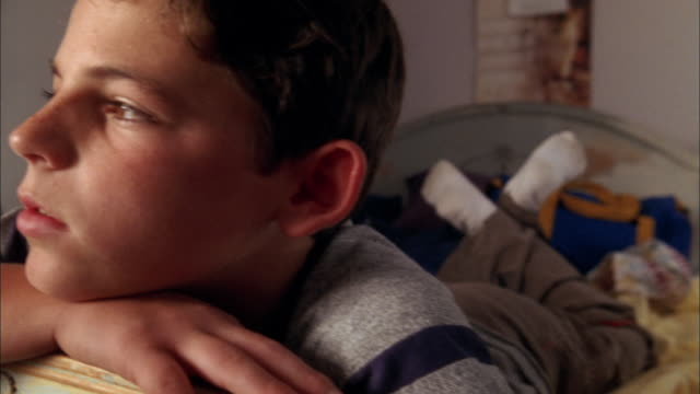 vidéos et rushes de close up boy lying on stomach in bed and looking at cam - rêvasser