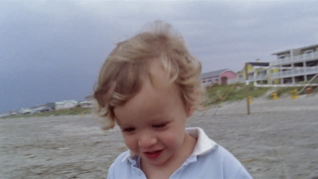 close up boy playing on beach and looking at camera/ charleston, south carolina - solo un bambino maschio video stock e b–roll