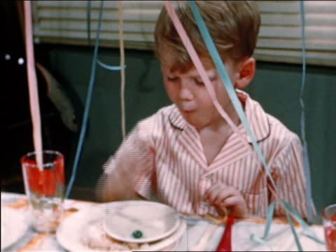 stockvideo's en b-roll-footage met 1946 close up boy sitting at table eating with fingers at party / industrial - 1946